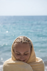 Woman wrapped in towel at sea