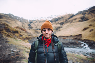 portrait of a young photographer taking photos of the beautiful mountain landscapes of iceland