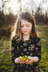 Pretty girl looking down at flowers in her hands