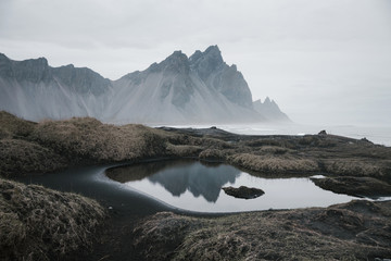 landscape of rocky mountains in Stokksnes with reflection on water, black sand beach with human steps, nobody empty wild area
