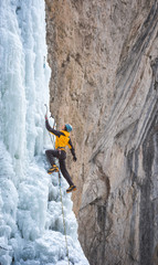 Male alpinist hanging on ice axe climbing on frozen waterfall