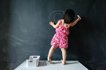 Toddler girl drawing on blackboard wall
