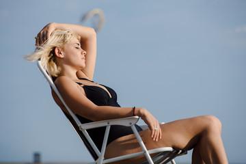 Beautiful woman suntanning on a beach chair