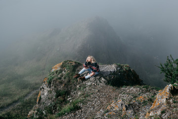 Anonymous woman posing on misty cliff