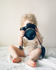 Curly kid with photo camera on bed