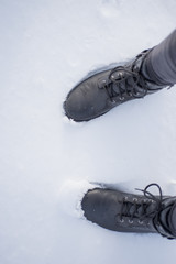 Boots in snow, close-up of black shoes from above