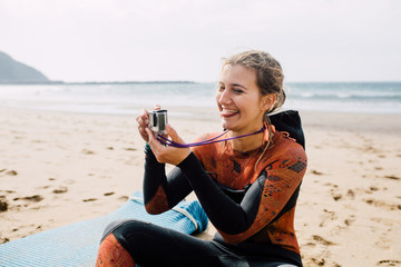 Woman in wetsuit taking a photo with action camera