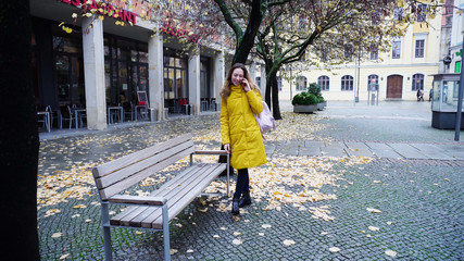 Fine girl talks on phone and goes to wooden bench, sits down and reports  affairs and impressions about city and excursion to  friend. Young European-looking woman with long blond hair smiles and si