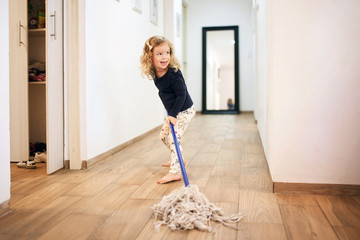 Young happy girl helping to clean the hallway