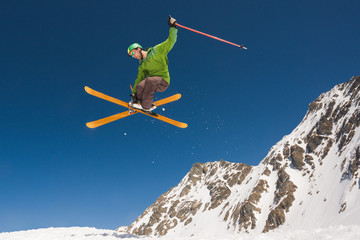 Man performing skiing helicopter trick against the blue sky