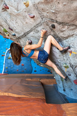 Sportswoman ascending artificial wall.