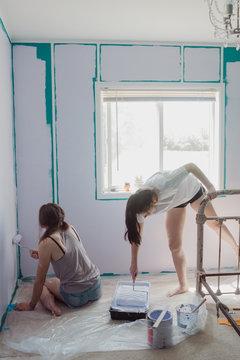 teenagers painting bedroom wall