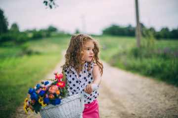 young girl driving bicycle with flowers basket