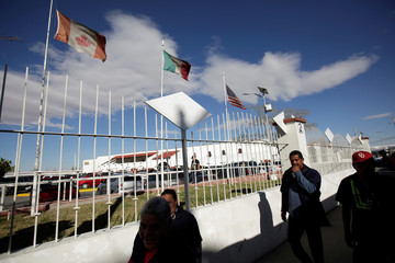 Workers walk by the flags of Canada, Mexico and U.S. flying at an assembly factory in Ciudad Juarez