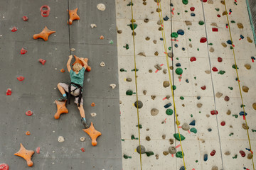 Little boy conquering climbing wall