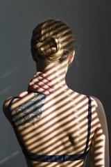 Unrecognizable woman in shadow lines