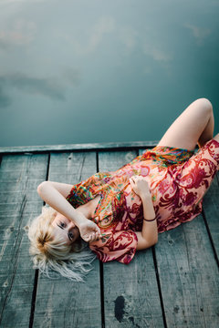 Young woman laying on the wooden dock