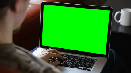 Man Using Laptop with Chroma Green Screen