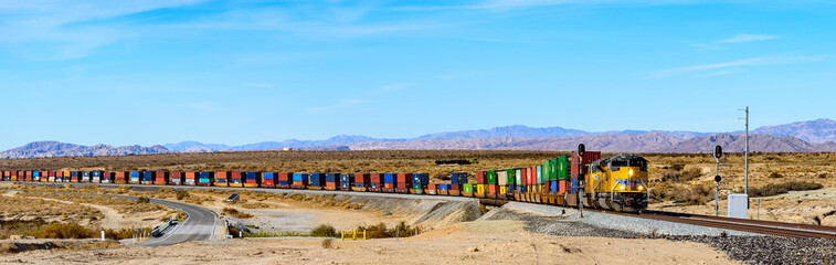 Wide panorama of Union Pacific railroad locomotive carrying long freight cars