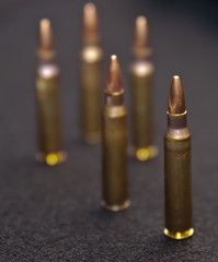 Five .223 rounds on a black background