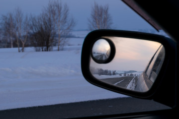 reflection in rear view mirror of night road, hills and sunset