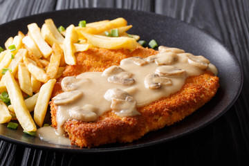 Traditional hunter schnitzel with sauce and fries close-up on a plate. horizontal