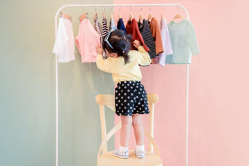 Soft Focus of a Two Years Old Child Choosing her own Dresses from Kids Cloth Rack Wall mural