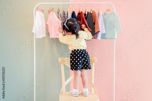Wall mural Soft Focus of a Two Years Old Child Choosing her own Dresses from Kids Cloth Rack