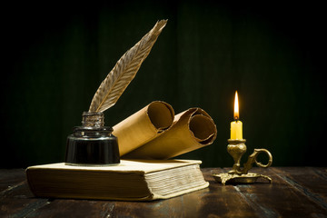 Education and writing concept, pen in ink bottle and candle holder with candle on wooden table.