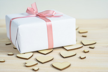 Gift wrapped in white paper with pink satin tape on background of wooden hearts
