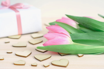 Light wooden desktop with wooden hearts, pink tulips and gift wrapped in white paper with satin ribbon