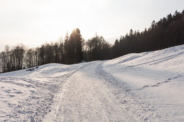 Photo of snowy landscape with blue sky and road in winter