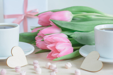 Romantic photo with pink tulips, two cups of coffee and wooden tiny hearts in the foreground