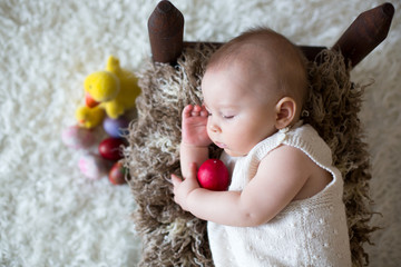 Cute little toddler baby boy, sleeping with colorful easter eggs and little decorative ducks