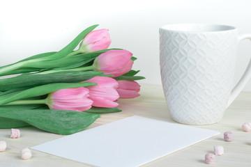 Soft feminine desktop with pink tulips, designer mug and postcard