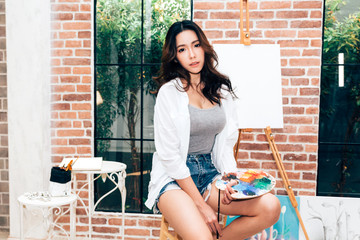 Young woman artist posing with empty canvas and paintbrush at home