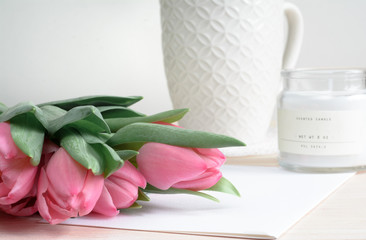 Spring composition with pink tulips and white candle, ceramic mug and card