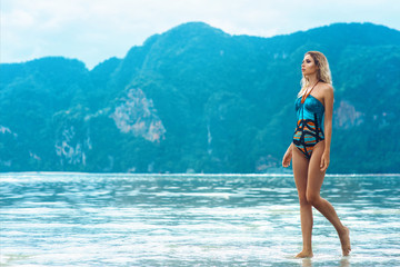 Sexy young beautiful russian girl in bright swimsuit walking on the sea water. Slim body woman on tropical beach in Thailand. Model vacation photo shoot. Blue sea coral white sand. Tanned skin