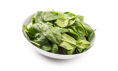 Spinach. Fresh baby spinach leaves in plate isolated on white