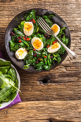Spinach Salad. Fresh spinach salad with eggs chili pepper and sweet cranberries.