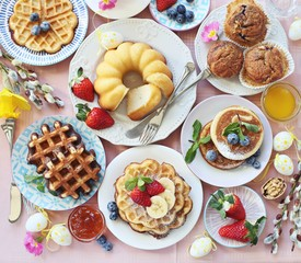 Easter dessert table. Pancakes,waffles and bundt cake with fresh berries and various of topping. Overhead view, copy space