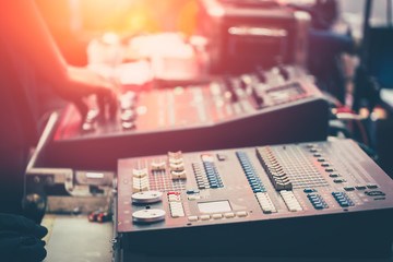 professional stage sound mixer closeup at sound engineer hand using audio mix slider working during concert perfomance