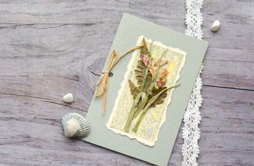 Composition from a card with a herbarium, shells, cotton lace and dry flowers. Vintage photo in delicate pastel silver pink tones.Gentle congratulations in the romantic style of chabby chic