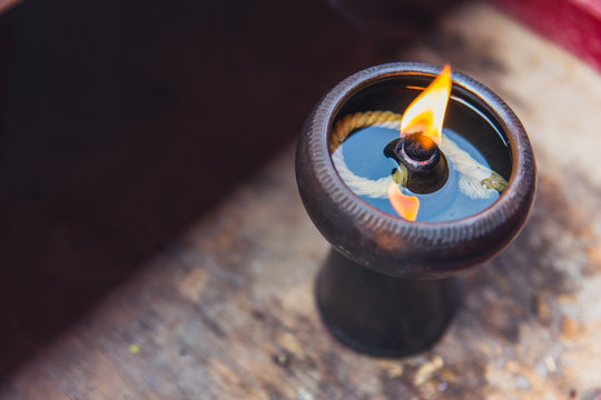 Ancient oil lamp made in clay on wood table