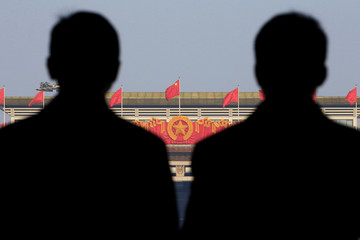 Security personnel are seen silhouetted during the third plenary session of the Chinese People's Political Consultative Conference (CPPCC) at the Great Hall of the People in Beijing