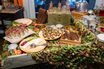 buffet in the form of military field cuisine: hay, military helmets, first-aid kit, camouflage
