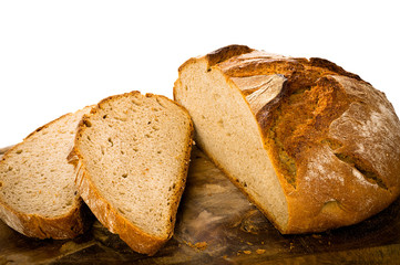 Loaf of rustic german bread on wooden board, isolated on white