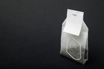 A mockup organic tea in a paper bag on a black background.