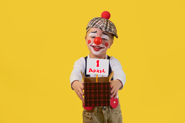 Kid clown with red nose 5 years on the bright yellow background. Little child holds box with white sheet, text 1 April. Concept birthday, holiday, celebration, party. Happy jester looking small box.