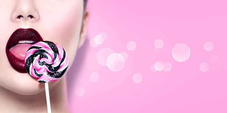Sexy beauty girl eating lollipop. Glamour model woman licking sweet colorful lollipop candy over pink background